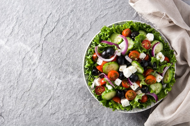 ブラックオリーブ、トマト、フェタチーズ、キュウリ、タマネギのグレーcopyspaceプレートで新鮮なギリシャ風サラダ