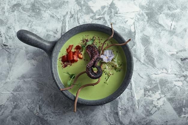Взгляд сверху суп спаржи с осьминогом в сером шаре на конкретном мраморном сером цвете. copyspace, реклама еды, мягкий свет.