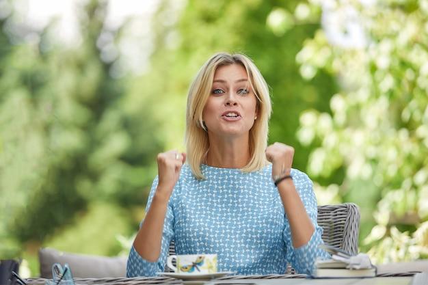ビジネスの女性は、サマーテラスのテーブルでコーヒーを飲みながら緊張して座っています。 copyspace、グリーン。