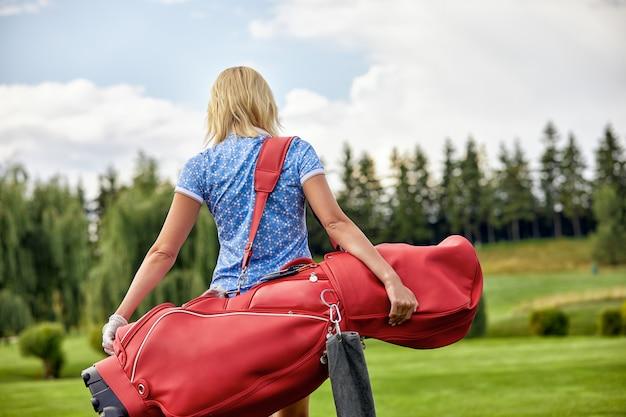 目標、copyspace。グリーンフィールドでゴルフ用品を保持している女性のゴルフ時間。卓越性、個人の職人技、ロイヤルスポーツ、スポーツバナーの追求。