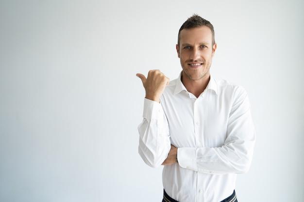彼の背後にあるcopyspaceを指す明るい起業家。