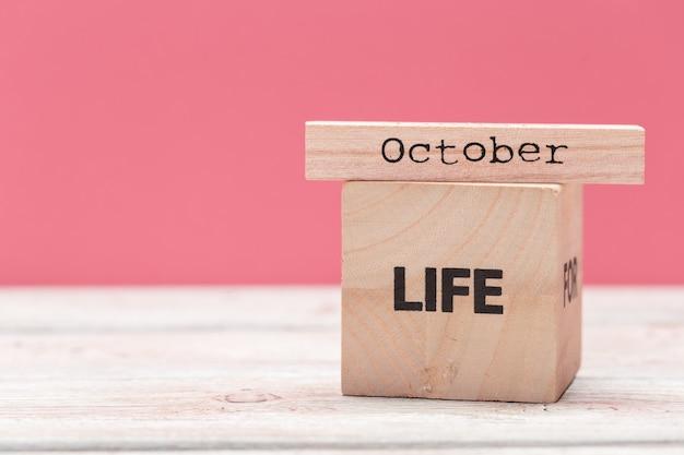 Деревянные кубики с текстом на столе над розовым с copyspace для текста