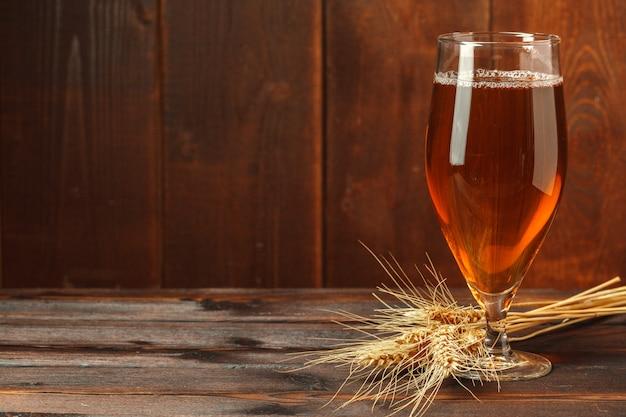 Стеклянное пиво на деревянной стене с copyspace