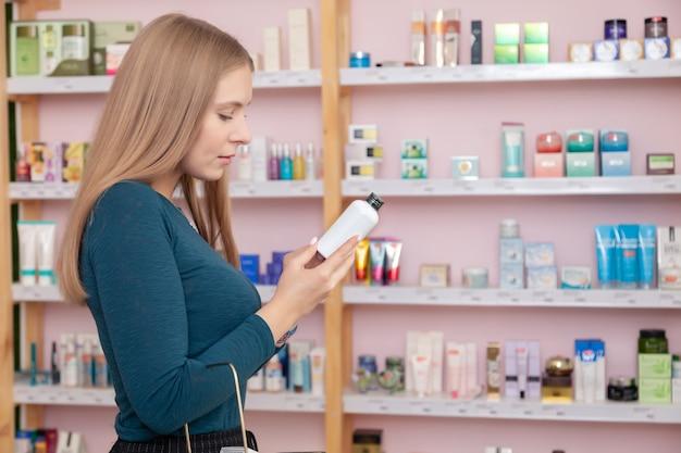 スキンケア化粧品、フェイスクリーム、血清を持つボックスを保持している美しい若い女の子のクローズアップの肖像画。テキスト、copyspaceの場所。高級自然化粧品店の写真