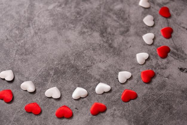 黒い石に小さな赤と白の心。 copyspaceとバレンタインデーのフレーム