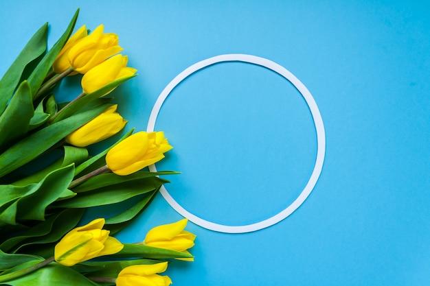 Круглая рамка и желтые тюльпаны на синем фоне copyspace