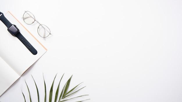 デスクトップフラットレイアウト。白い背景の上のメモ帳、時計、メガネ、手のひら。 copyspace。