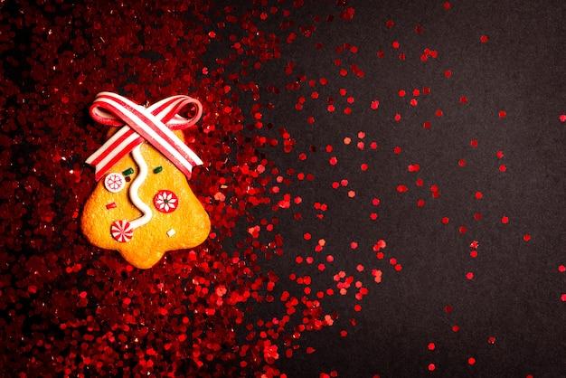 黒に赤のキラキラとジンジャーブレッドベルのクリスマスの装飾。上面図。 copyspaceでフラットレイアウト