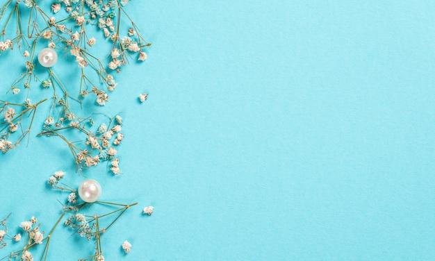 花の組成を持つカード。パステルブルーのカスミソウの花。フラット横たわっていた、トップビュー、copyspace