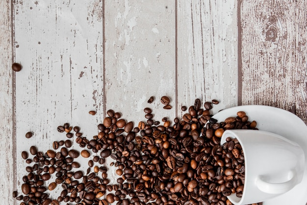 白いカップと明るい木製の背景にコーヒー豆のブラックコーヒー。トップビュー、copyspace