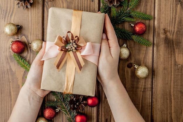 クリスマスギフトボックス、紙のロール、赤の装飾。休日の準備。 copyspaceのトップビュー。ギフト用の箱を保持している女性の手