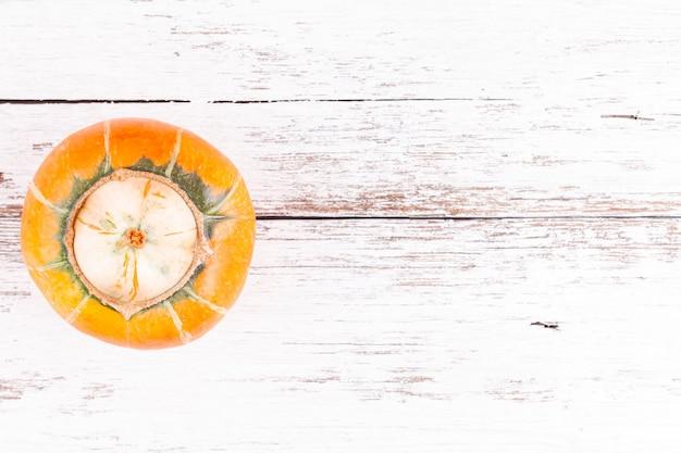 Уродливая тыква с мутацией другой тыквы внутри на деревянный стол с copyspace