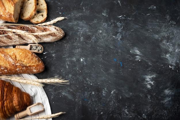 Ассортимент свежего хлеба, хлебопекарных ингредиентов. натюрморт запечатлен сверху. здоровый домашний хлеб. фон с copyspace.