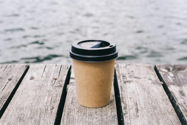 Бумажный стаканчик кофе на коричневой деревянной и предпосылке моря. copyspace