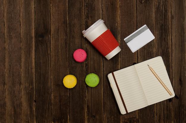 木製の背景に鉛筆、マカロン、紙コップ、クレジットカードでノートブックを開きます。トップビュー、copyspace