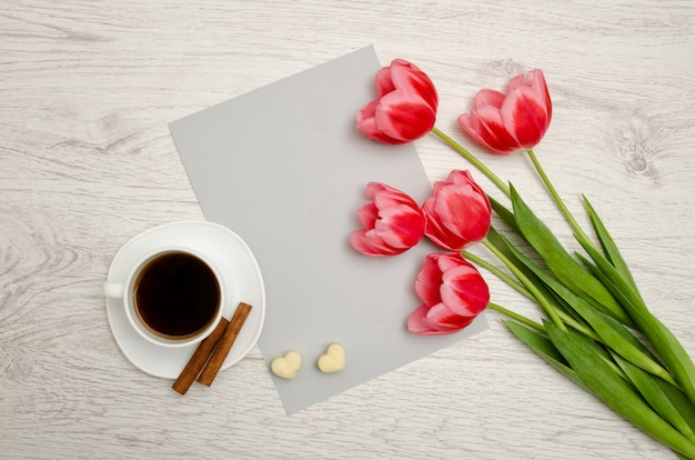 Розовые тюльпаны на чистый лист бумаги, кружка кофе и зефир, светлый деревянный. вид сверху, copyspace