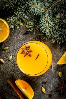 秋、冬のカクテル、シナモン、アニススター、カルダモン、クローブとホットスパイシーな冬のオレンジパンチ。ガラスの食材とクリスマスツリーの枝を持つ黒い石のテーブル。 copyspaceトップビュー