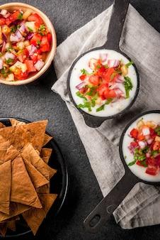 Мексиканская, латиноамериканская кухня. рецепт кесо бланко - сливочный сыр, сливки, тушеные овощи, помидоры, лук, перец, зелень. с печеными чипсами из тортильи, стол из черного камня. вид сверху copyspace