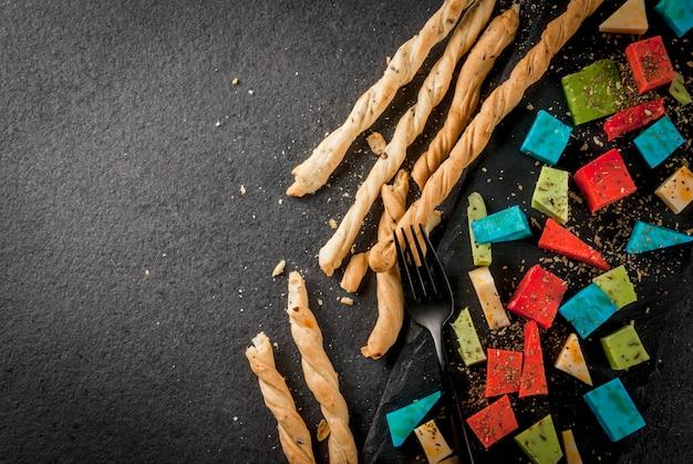 Модная современная еда. разноцветный красочный голландский сыр - голубой (лаванда), красный (острый перец), зеленый (базилик), классический желтый сыр. с хлебными палочками, бокалом, черным столом. copyspace вид сверху