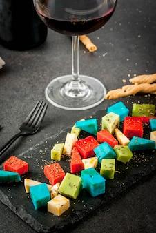 Модная современная еда. разноцветный органический голландский сыр - голубой (лаванда), красный (острый перец), зеленый (базилик), классический желтый сыр. с хлебными палочками, бокалом, черным столом. copyspace