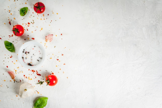 Продовольственный фон. ингредиенты, зелень и специи для приготовления обеда, обеда. листья свежего базилика, помидоры, чеснок, лук, соль, перец. на белом каменном столе. copyspace вид сверху