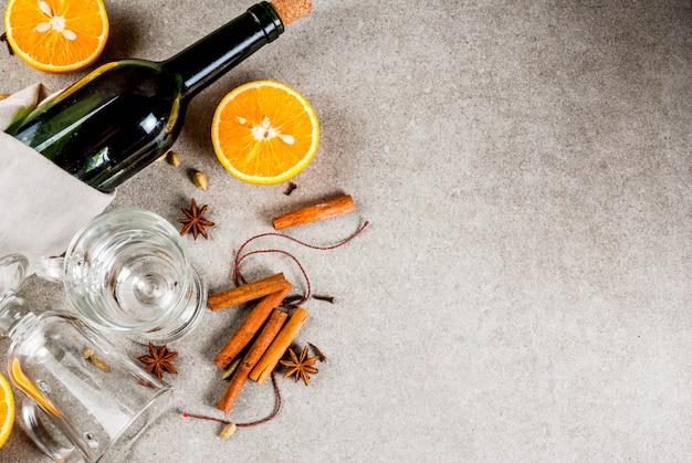 Рождественские рецепты горячих напитков, набор ингредиентов для глинтвейна: бутылка вина, стеклянные чашки, специи, апельсин. серый каменный фон, вид сверху copyspace