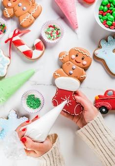Готовясь к рождеству, девушка (руки на картинке) украшает домашние традиционные пряники ручной работы с разноцветной сахарной глазурью, печеньем, белым мраморным столом. вид сверху copyspace