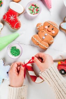 クリスマスの準備として、女の子(写真の手)は手作りの手作りの伝統的なジンジャーブレッドに、色とりどりの砂糖のアイシング、ビスケット、白い大理石のテーブルを飾ります。トップビューcopyspace