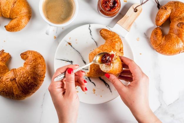 女の子は自家製のコンチネンタルブレックファースト、クロワッサン、コーヒーを食べます。白い大理石のテーブル、copyspaceトップビュー、写真の手にジャムします。