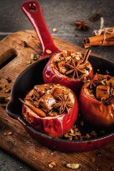秋の料理のレシピ。グラノーラ、タフィー、スパイスを詰めた焼きりんご。黒い石のテーブル、フライパン、copyspace