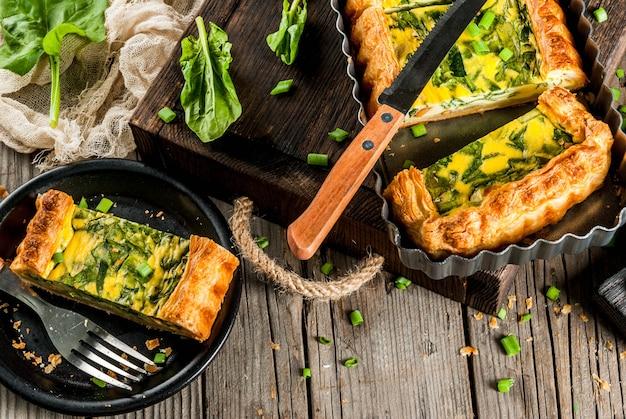フランスの家庭料理。キャセロール。パイ。若いねぎとほうれん草が入った、パイ生地のキッシュロレーヌ。古い木製の素朴なテーブル。切る。焼くための形で。皿、フォーク、ナイフ。 copyspaceトップビュー