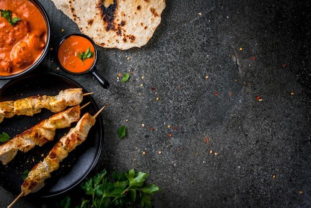 Индийская еда. традиционное блюдо с пикантной курицей, тикка масала, сливочное куриное карри, с индийским нааном, сдобным хлебом, специями, зеленью. подается в миске. соус, на шампурах. каменный темный стол. copyspace вид сверху