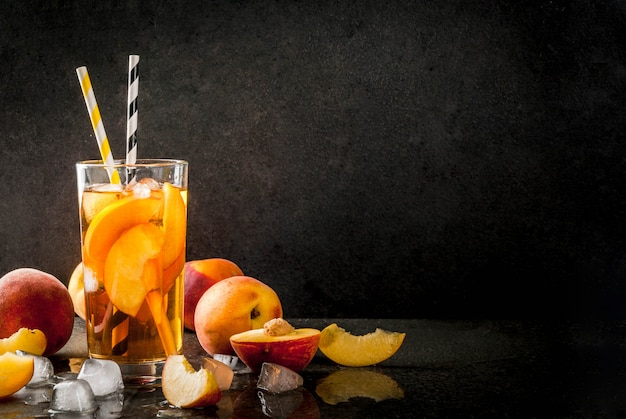 Летние прохладительные напитки. холодный чай с кусочками органического домашнего персика нектарина. на черном каменном фоне, со льдом и ингредиентами. copyspace