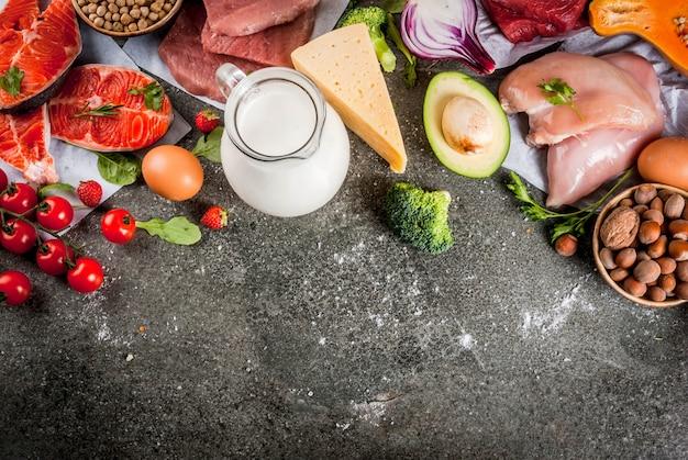 健康的なダイエット 。有機食材、スーパーフード:牛肉と豚肉、鶏肉の切り身、サケ、魚、豆、ナッツ、牛乳、卵、果物、野菜。黒い石のテーブル、copyspaceトップビュー