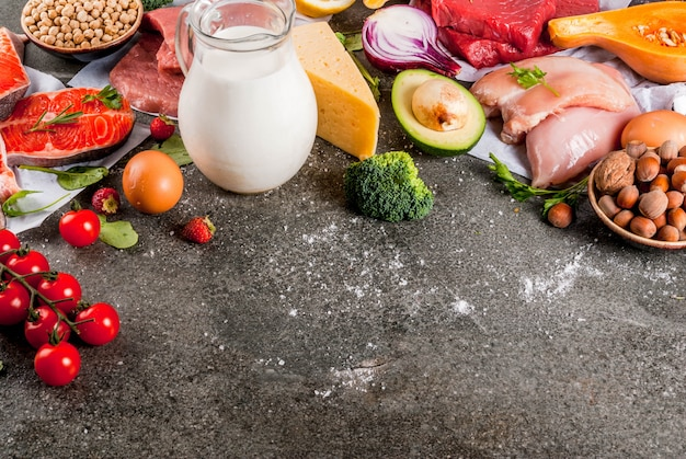 健康的なダイエット 。有機食材、スーパーフード:牛肉と豚肉、鶏肉の切り身、サケ、魚、豆、ナッツ、牛乳、卵、果物、野菜。黒い石のテーブル、copyspace
