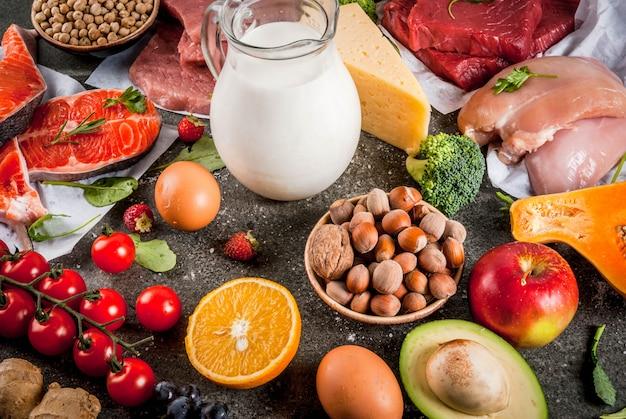 Здоровая диета . органические пищевые ингредиенты, суперпродукты: говядина и свинина, куриное филе, лосось, фасоль, орехи, молоко, яйца, фрукты, овощи. стол из черного камня, copyspace