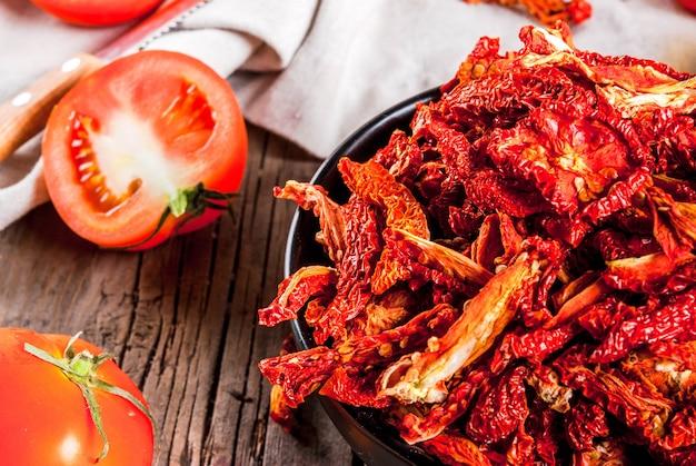 Домашние сушеные органические помидоры, хрустящие томатные чипсы, на старый деревенский деревянный стол со свежими помидорами и оливковым маслом. copyspace