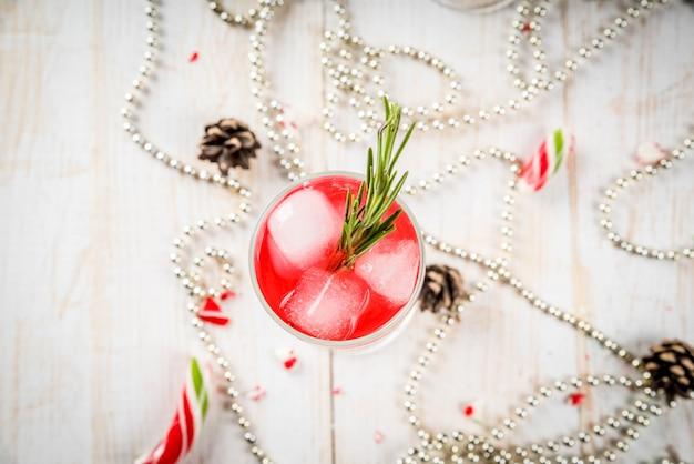 お正月、クリスマスの飲み物。クランベリー、リキュール、ローズマリー、氷と赤いアルコールカクテル。クリスマスキャンディー、装飾品、松ぼっくりのある白いテーブル。 copyspaceトップビュー