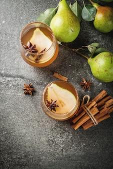 秋の飲み物。グリューワイン。ナシ、サイダー、チョコレートシロップ、シナモン、アニス、ブラウンシュガーと伝統的な秋のスパイシーなカクテル。黒い石のテーブルの上。 copyspaceトップビュー