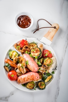 バーベキュー。野菜バーベキューきのこ、トマト、ズッキーニ、タマネギとさまざまな肉のグリルソーセージの品揃え。白い大理石のテーブルの上、皿の上、ソース付き。 copyspaceトップビュー