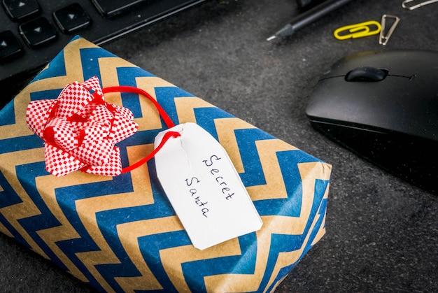 Празднование рождества в офисе, идея обмена дарами секрета санта. клавиатура, мышка, блокнот, ручки, карандаши, рождественский подарок. черный офисный стол, copyspace