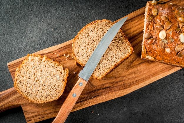 黒い石のテーブルにまな板の上のカボチャの種と焼きたての自家製有機マルチグレインのパン。 copyspaceトップビュー