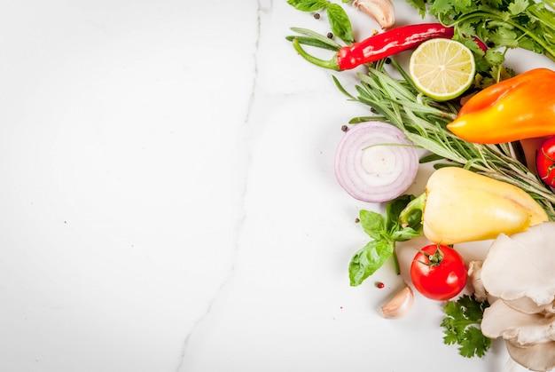 Приготовление пищи, стол из белого мрамора. свежие сырые органические овощи (помидоры, перец, грибы, лук), зелень, специи, лайм для приготовления обеда. вид сверху copyspace
