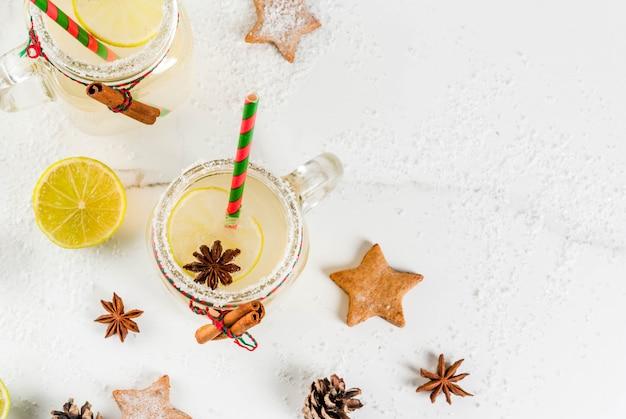 秋と冬の飲み物。クリスマスの休日の飲み物。ライムジュース、シナモン、リキュール、砂糖、アニスの星が付いたお祝いスノーボールカクテル。クリスマスの装飾、copyspaceトップビューで白いテーブルの上