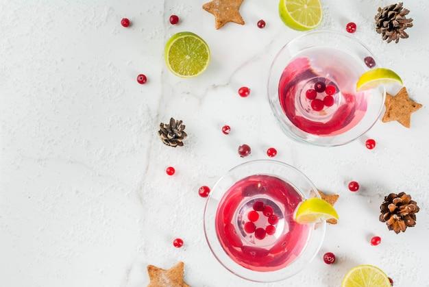秋と冬の飲み物。クリスマスの休日の飲み物。お祝いクランベリーマティーニとライム。クリスマスの装飾、copyspaceと白いテーブルの上