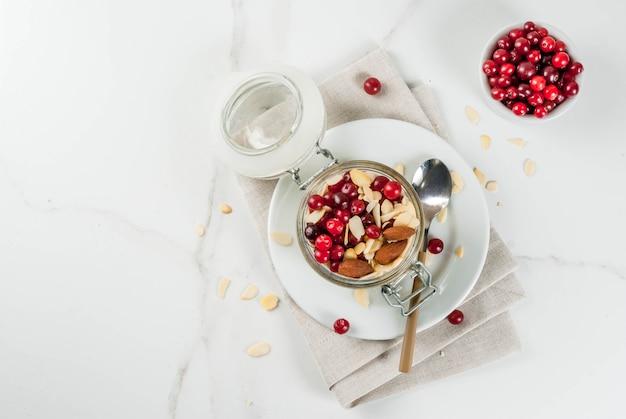 冬の健康的な朝食のレシピ、クリスマスの朝のアイデア。アーモンド、クランベリー、砂糖を一晩オートミール。 。 copyspaceトップビュー