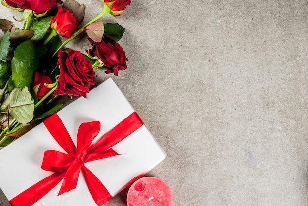 休日、バレンタインデー。赤いバラの花束、赤いリボンとネクタイ、ラップされたギフトボックスと赤いろうそく。灰色の石のテーブル、copyspaceトップビュー