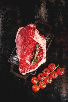 新鮮な生肉、グリルパンボード上のラムビーフマーブルステーキ、調理用食材。さびた金属テーブル、copyspaceトップビュー