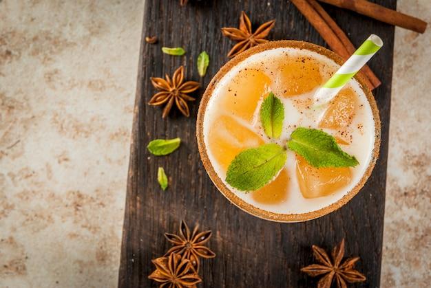 インドの伝統的な飲み物は、チャイ、ミルク、ミントの葉のアイスキューブを添えたアイスティーまたはチャイマサラです。木の板に縞模様のストローで。ライトベージュの石のテーブルの上。 copyspaceトップビュー