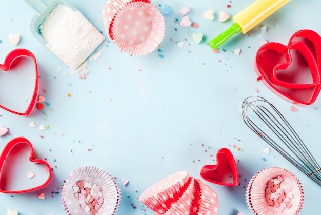 Сладкая выпечка на день святого валентина, приготовление с выпечкой - со скалкой, венчиком для взбивания, формочками для печенья, сахарной посыпкой, мукой. голубой фон, вид сверху copyspace
